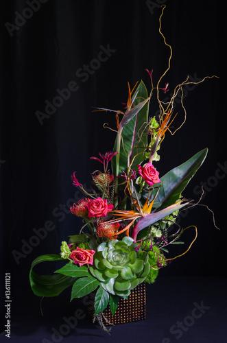 Foto op Canvas Bloemen Lavish floral arrangement on black background.