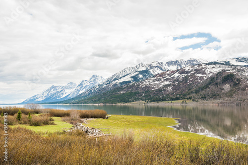 Photo  Grand Teton mountains with lake and dark, stormy cloudy, overcast sky