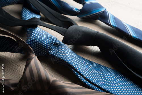Fotografia  Silk neck ties on wooden background.