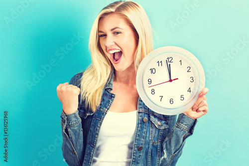 Photo  Woman holding clock showing nearly 12