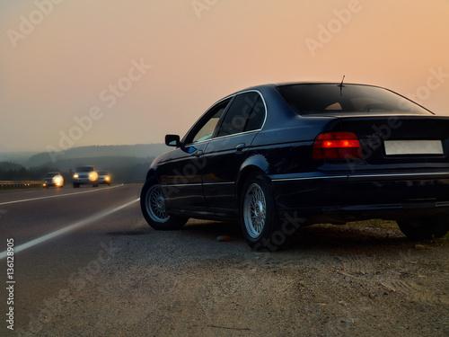Автомобиль седан на трассе на фоне заката Canvas Print