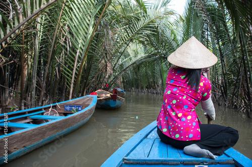 Obraz na plátně Young Woman paddling along the Mekong River in Vietnam