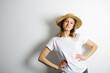 Joyful girl in a straw hat standing hands on waist