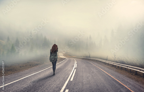 Fotografía  girl walking alone on mountain highway in winter foggy day