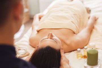 Obraz na płótnie Canvas Masseur looking at patient back view. Young woman in towel only lying on massage table and ready for relaxing procedures, blurred massagist back in side of photo. Beauty industry concept