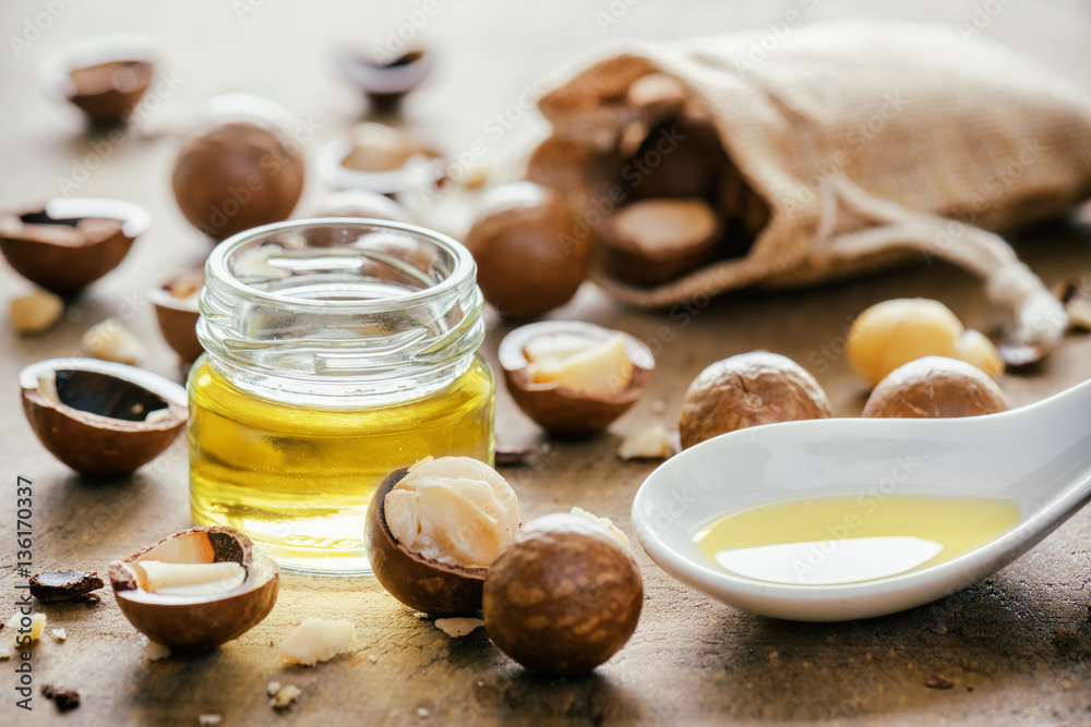 Fototapety, obrazy: Natural macadamia oil and nuts on wooden board. Healthy product