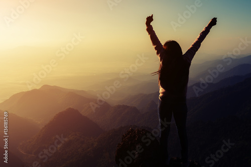 In de dag Ochtendgloren silhouette woman rising hands on mountain in morning with vintag