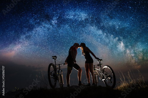 Romantic night. Kiss of couple with mountain bicycles under starry sky. Night landscape with colorful Milky Way. Bottom view