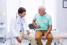 Senior Man Showing Stomach Ache Pain To Doctor