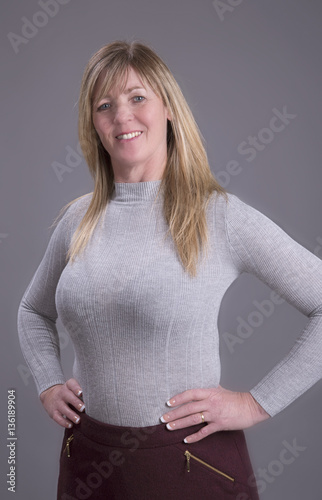 Attractive Middle Aged Busty Woman With Hands On Waist Wearing A Tight Grey Jumper -4107