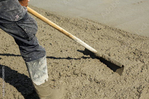 Fotografie, Obraz  Spreading out freshly poured concrete with a shovel
