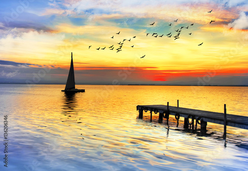 Tuinposter Pier los colores del atardecer sobre el mar en calma