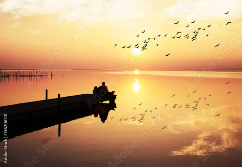 Tuinposter enamorados mirando la puesta de sol
