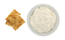 Seasoned Rosemary And Olive Oil Crackers With A Bowl Of French Onion Dip Top View Isolated On A White Background.