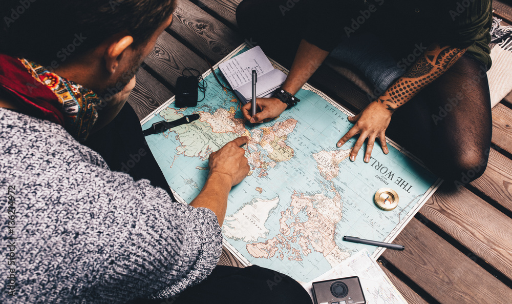 Fototapety, obrazy: Couple making vacation plan sitting by the world map.