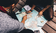 Couple Making Vacation Plan Sitting By The World Map.