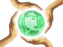 Four Circular Female Hands Around A Green Glass Globe
