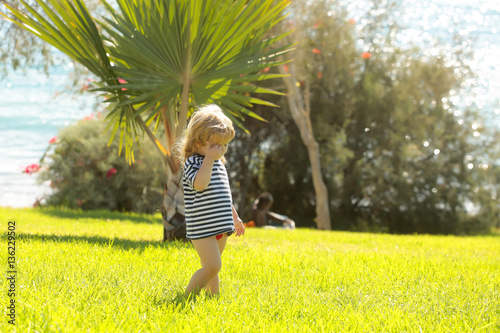 Poster Palmier Cute baby boy in striped tshirt walks on green grass