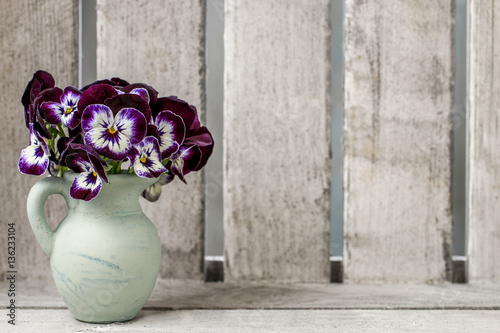 Bouquet of pansy flower in ceramic vase. Wooden background