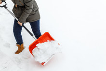 Woman With Shovel Cleaning Sno...