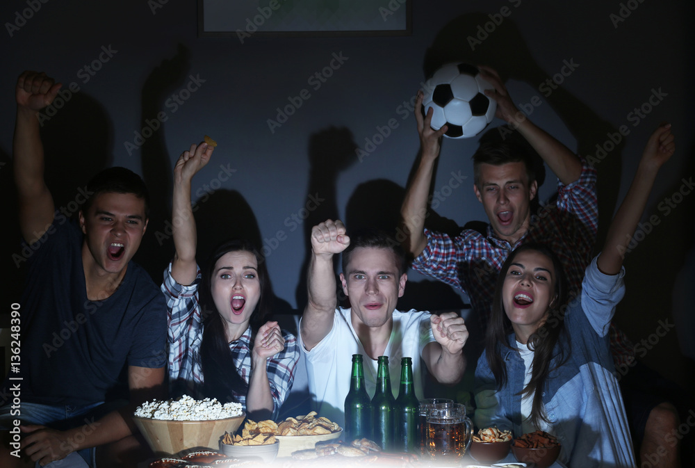 Fototapety, obrazy: Young fans watching football match on TV late in evening with beer and snacks