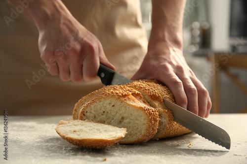 Foto op Canvas Bakkerij Male hands cutting wheaten bread, closeup