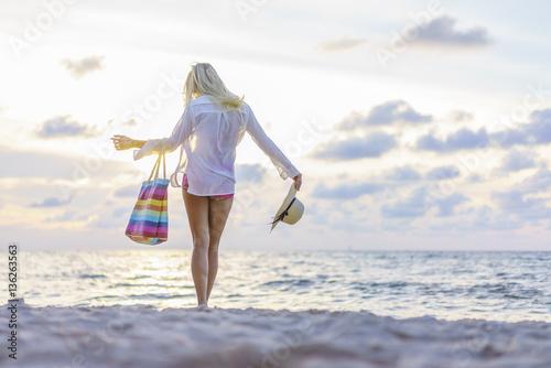 Fotografia  Woman on the beach at sunset