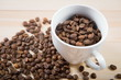 coffee beans in cup. Coffee cup and coffee beans on wooden background. coffee with cinnamon, coffee with additives. Coffee beans and cinnamon sticks