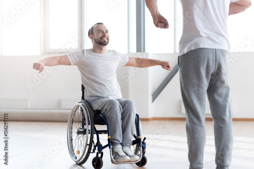Fotografía  Attentive disabled man training in the gym with the orthopedist