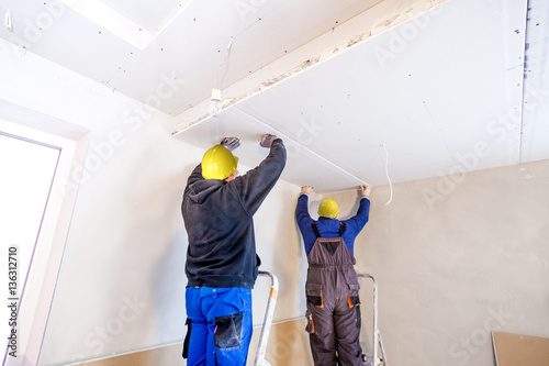 Fotografie, Tablou  Workers assemble a suspended ceiling with drywall