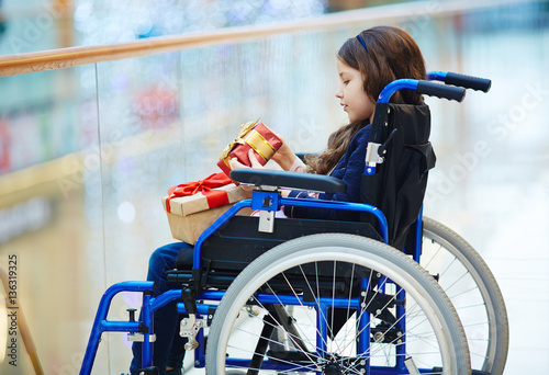 Valokuva  Side-view of disabled child in wheelchair looking at gift-box