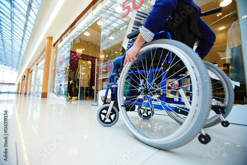 Fototapeta Disabled shopper moving in wheelchair along departments in the mall