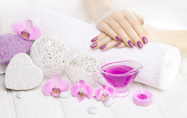 Obraz na płótnie Canvas beautiful pink manicure with orchid and towel on the white wooden table. spa