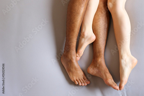 Tablou Canvas Legs of interracial couple in bed - copy space