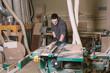 Carpenter working on a saw machine in his workshop