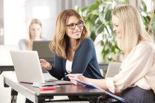 Brainstorming In The Office. Shot Of  Two Businesswoman Talking And Working Together At A Workstation In An Office