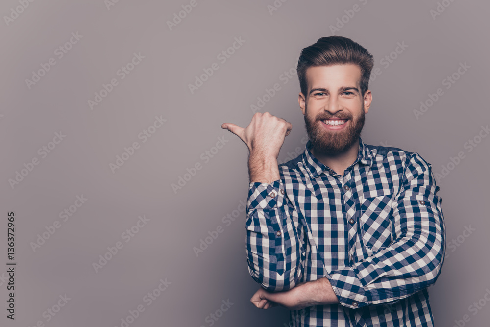 Fototapeta Cheerful toothy bearded stylish man pointing with finger