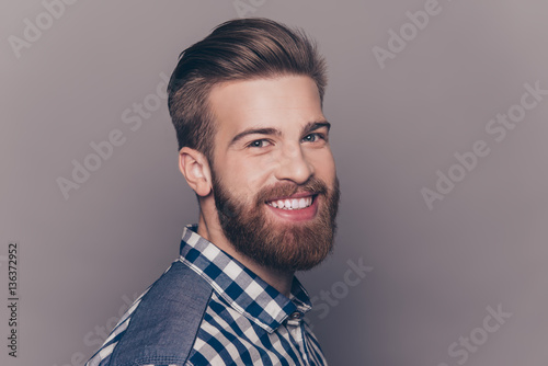 Valokuva  Side view portrait of cheerful stylish man with beaming smile