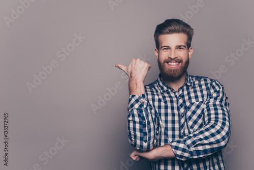 Fototapeta Cheerful toothy bearded stylish man pointing with finger obraz