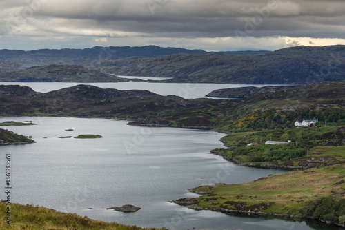 Printed kitchen splashbacks Lake Assynt Peninsula, Scotland - June 7, 2012: Under blue-gray cloudy sky aerial view on Loch Ardhair with intrusion of the ocean in the wild landscape of hills, mountains, bare land, small islands.