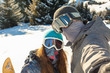 Couple snowboarder standing on a mountain top at sunset and maki