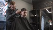 Handsome man doing a haircut for man with black hair at barber shop, modern hair stylist, close up.