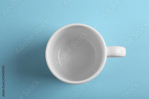 Blank ceramic cup on color background