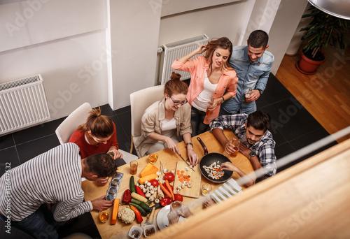 Zdjęcie XXL Młoda grupa przyjaciele w kuchni przygotowywa wpólnie jarskiego posiłek. Domowy przyjęcie.