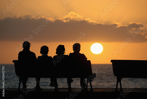 Fotografía  Silhouette of a group of seniors who sits on the bench, looking at the sunset
