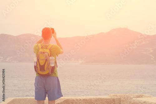 Fototapeta Man with a backpack photographs on the phone the sea and mountains obraz na płótnie