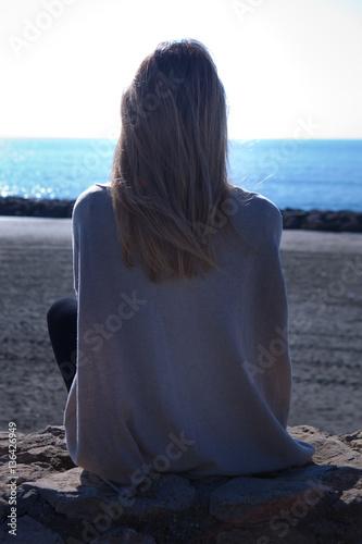 Donna Seduta Di Spalle Sugli Scogli Guarda Il Mare Buy This Stock