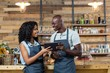 Smiling waiter and waitress using digital tablet at counter