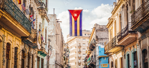 Canvas Print A cuban flag with holes waves over a street in Central Havana