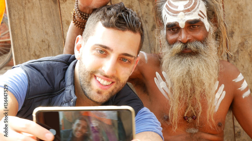 Photo Tourist taking a selfie with Sadhu - Holy Man, in Varanasi, India